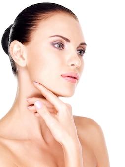 Piękna zdrowa twarz młodej całkiem białej kobiety z ręką na brodzie