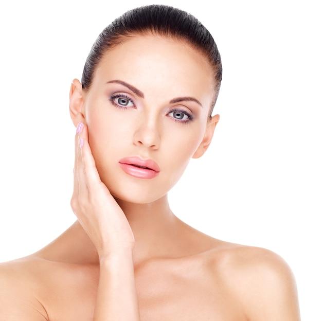 Piękna zdrowa twarz młodej całkiem białej kobiety ze świeżą skórą - na białym tle