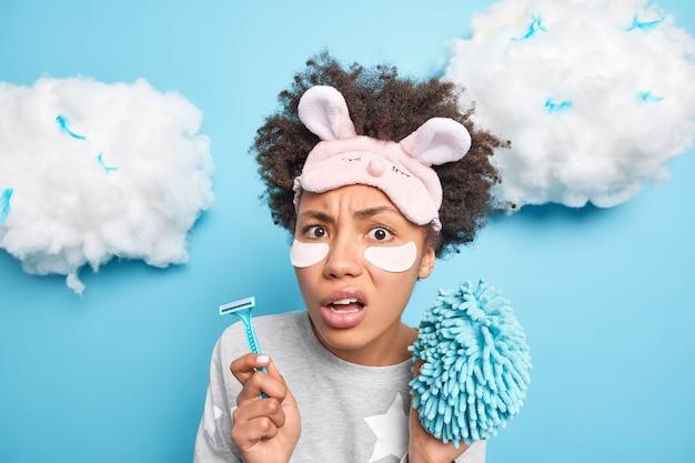 Piękna zdziwiona kobieta trzyma brzytwę i gąbkę, ubrana w piżamę i maskę do spania, będzie wykonywać codzienne czynności higieniczne, nakłada plastry kosmetyczne pod oczy odizolowane na niebieskiej ścianie