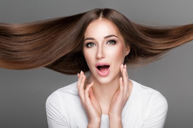 Piękna zdziwiona kobieta z przepięknymi lśniącymi długimi włosami latającymi. pielęgnacja włosów