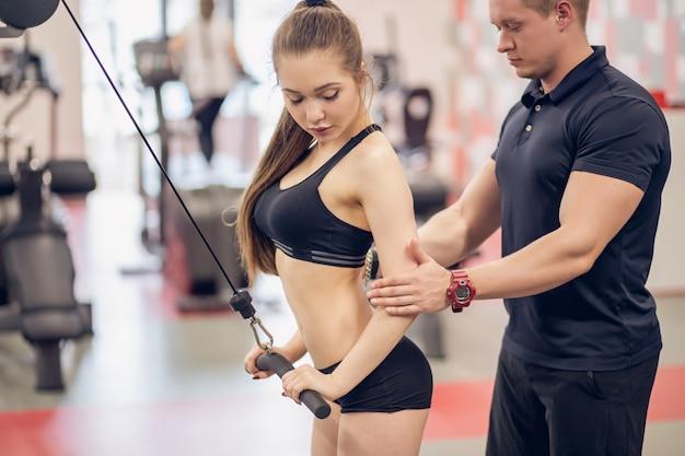 Piękna żeńska atleta z jej trenerem lub trenerem ćwiczy przy skrzyżowaniem kabla