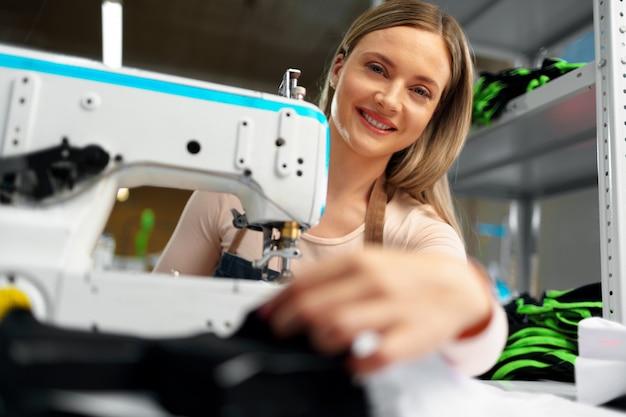 Piękna żeńska krawcowa pracuje z tkaniną przy jej miejscem pracy
