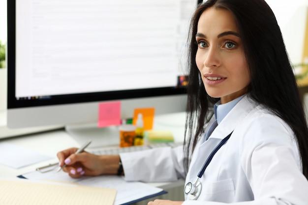 Piękna żeńska lekarz ogólny robi notatki podczas przyjmowania gościa