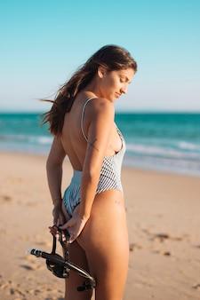 Piękna żeńska pozycja na piaskowatej plaży