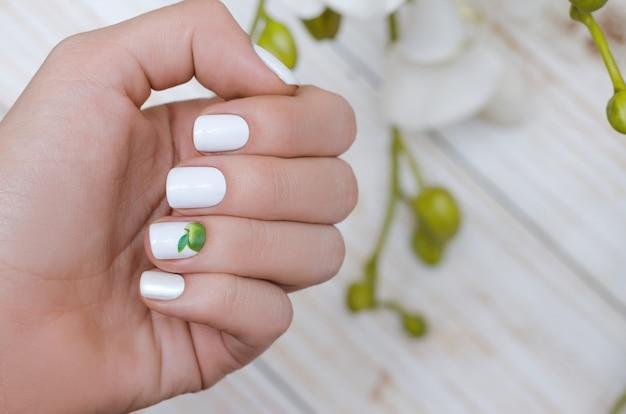 Piękna żeńska ręka z białym wzorem paznokci.