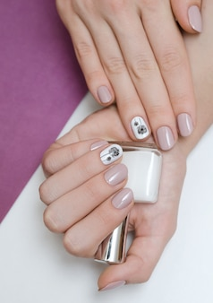Piękna żeńska ręka z dandelion gwoździa projektem.