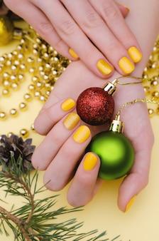 Piękna żeńska ręka z żółtym gwoździa projektem. świąteczny manicure.