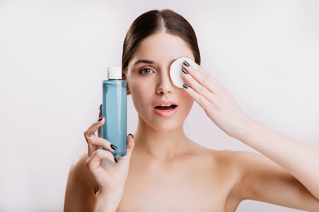Piękna zielonooka dziewczyna nałożyła kosmetyczną gąbkę na twarz, usuwając brud. portret zdrowej kobiety bez makijażu na białej ścianie.