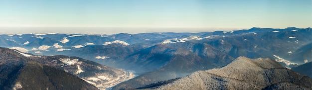 Piękna zimowa panorama ze świeżym śniegiem. krajobraz z sosny świerkowe, błękitne niebo ze światłem słonecznym i wysokie karpaty na tle.