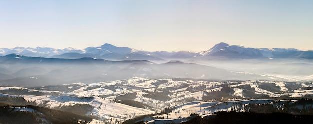 Piękna zimowa panorama ze świeżym śniegiem. krajobraz z świerkowymi sosnami, niebieskim niebem z słońca światłem i wysokimi karpackimi górami na tle.