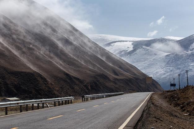 Piękna zimy droga w tybet pod śnieżną górą, sichuan, chiny