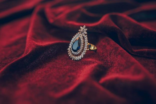 Piękna złota biżuteria z jem na czerwonym aksamitnym tle