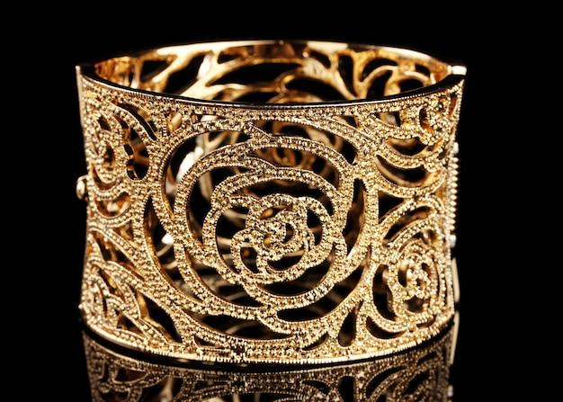 Piękna złota bransoletka na czarnym tle