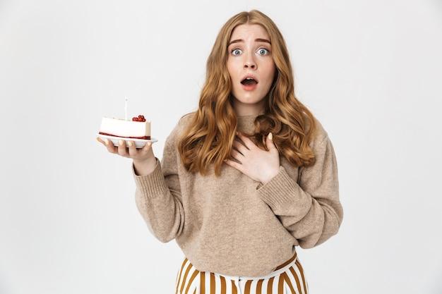Piękna zmartwiona młoda dziewczyna z długimi blond kręconymi włosami, ubrana w sweter stojący na białym tle nad białą ścianą, trzymająca tort urodzinowy