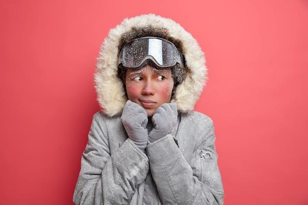 Piękna zmarznięta kobieta drży z zimna podczas śniegu i niskiej temperatury w lutym, ubrana w ciepłą szarą kurtkę i gogle narciarskie jeździ na snowboardzie w góry.