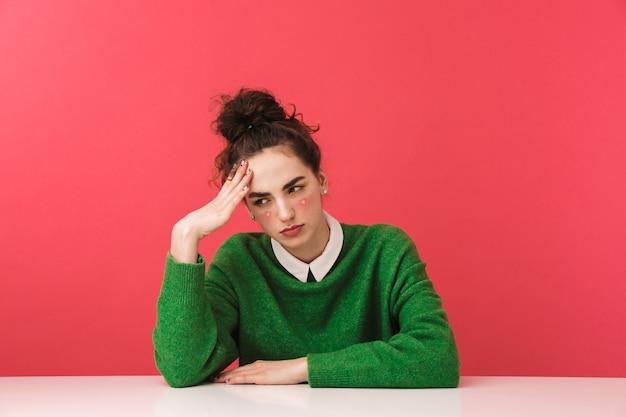 Piękna zmęczona młoda studentka dziewczyna siedzi przy stole na białym tle