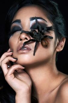 Piękna zmysłowa azjatykcia dziewczyna z pająkiem w studiu
