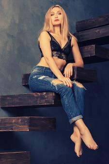 Piękna zmysłowa dorosła kobieta w staniku i dżinsach, pozowanie na drewnianych schodach wspornikowych. patrząc na aparat. koncepcja rozwoju osobistego