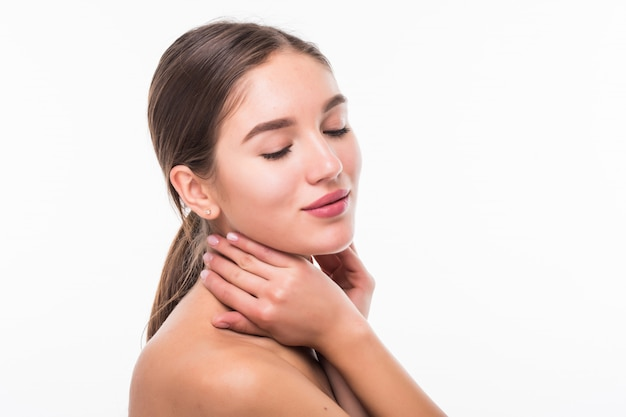 Piękna zmysłowa kobieta dotyka jej twarz odizolowywającą na biel ścianie. koncepcja pielęgnacji skóry i urody. spa.