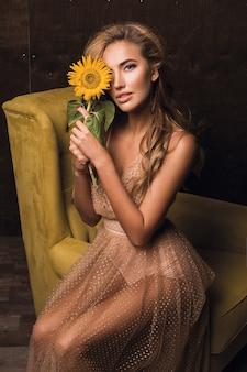 Piękna zmysłowa kobieta siedzi na fotelu i pozuje ze słonecznikiem