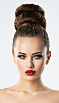 Piękna zmysłowa kobieta z kreatywną fryzurą. dość młoda dziewczyna dla dorosłych z brązowym makijażem oczu i czerwonymi ustami