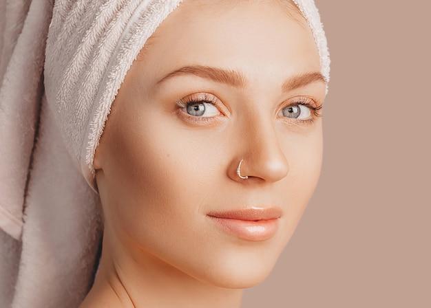 Piękna zmysłowa młoda dziewczyna z czystą skórą na beżowej ścianie