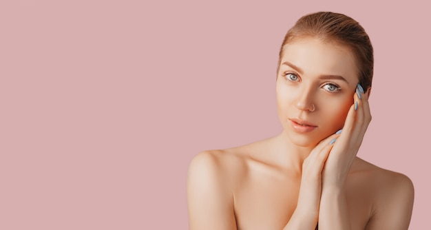Piękna zmysłowa młoda dziewczyna z czystą skórę na różowym tle z makieta. topless kobieta w ręczniku. koncepcja zabiegów spa, naturalne piękno i pielęgnacja, młodość, krem i maska, świeżość