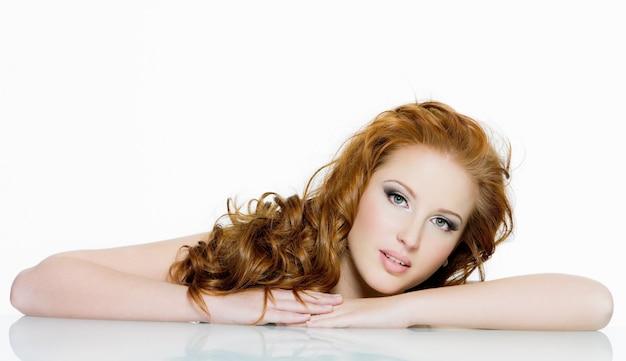 Piękna zmysłowa rudowłosa kobieta z długimi falującymi włosami - na białym tle