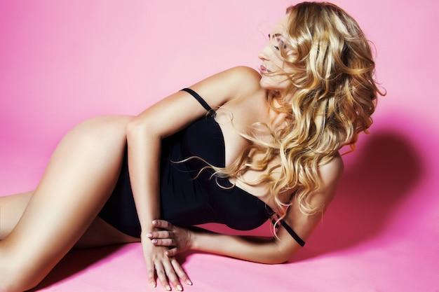 Piękna zmysłowa wspaniała młoda blondynka z modnym makijażem i fryzurą pozuje w czarnym body. dziewczyna z falującymi włosami. elegancka dama odizolowywająca na menchiach.