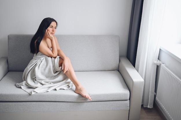 Piękna znudzona szczupła brunetka kobieta siedzi w wygodnej szarej kanapie pod ciepłym kocem w domu. kwarantanna samoizolacyjna podczas pandemii wirusa corona. covid19 zostań w domu, ratuj życie