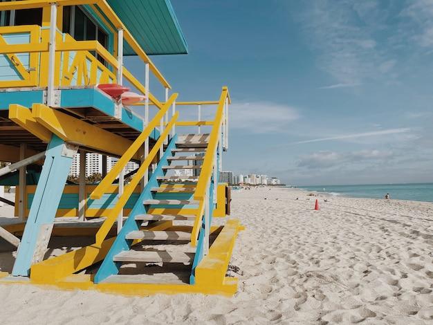 Piękna żółta i jasnoniebieska wieża ratownika pod pochmurnym słonecznym niebem w miami beach. floryda, usa