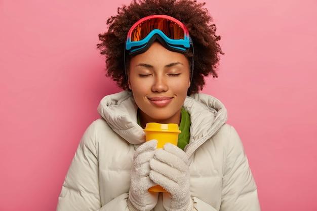 Piękna zrelaksowana dziewczyna z kręconymi włosami w białym fartuchu i rękawiczkach, pije gorący aromatyczny napój, nosi maskę snowboardową, ma sportowe ferie zimowe, odizolowane na różowym tle.