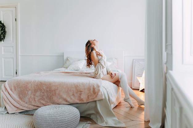 Piękna zrelaksowana kobieta w bieliźnie i legginsach na łóżku czeka na cud