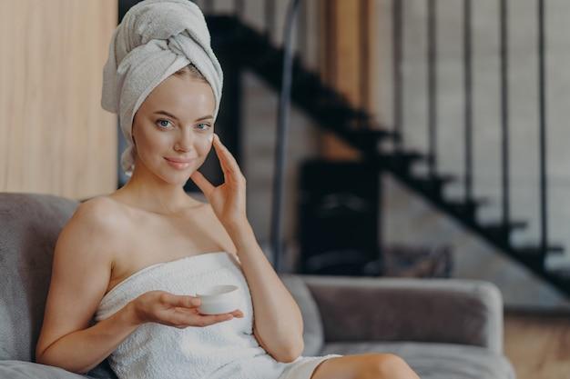 Piękna zrelaksowana kobieta zawinięta w ręcznik picia herbaty