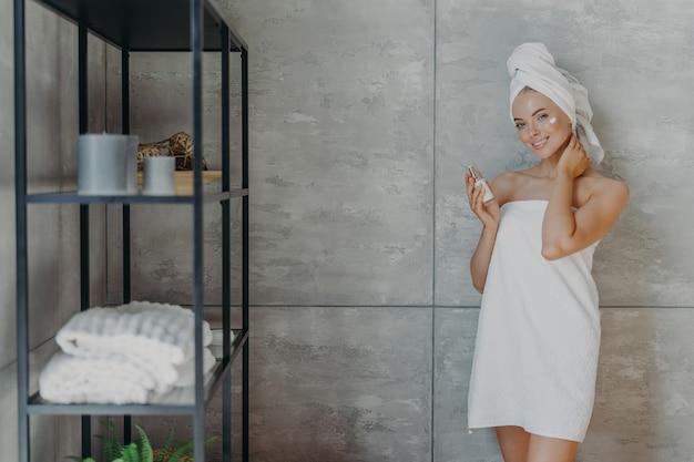 Piękna zrelaksowana kobieta zawinięta w ręcznik stosując krem do twarzy