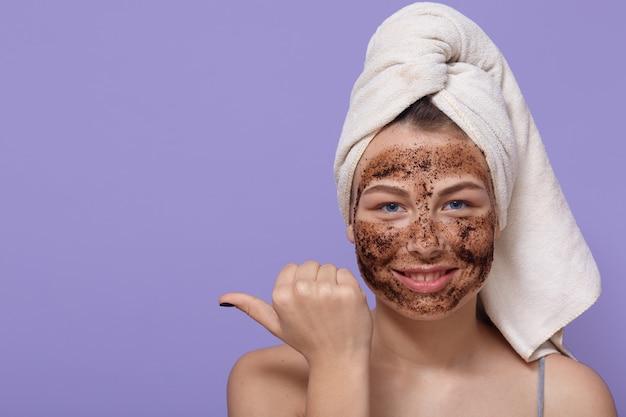 Piękna zrelaksowana uśmiechnięta kobieta wskazuje kciukiem palec na wolnej przestrzeni, nakłada na twarz naturalną czekoladową maskę
