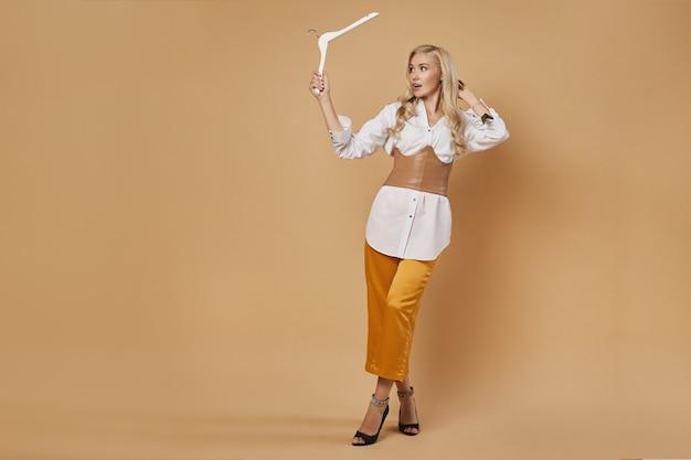 Piękna zszokowana młoda kobieta, seksowna blondynka w modnym stroju, z pustym wieszakiem w dłoniach, pozuje na beżowym żółtym tle