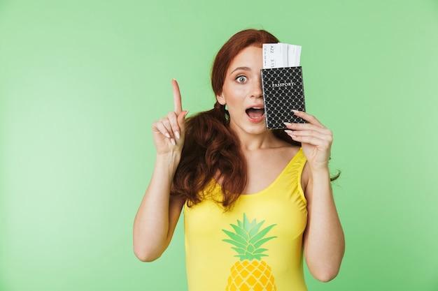 Piękna zszokowana młoda ruda dziewczyna pozuje na białym tle na tle zielonej ściany z paszportem i bilety.