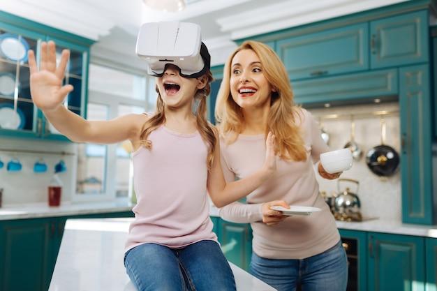 Piękna, żywiołowa jasnowłosa dziewczyna uśmiecha się i nosi zestaw vr, podczas gdy jej matka stoi za nią z filiżanką
