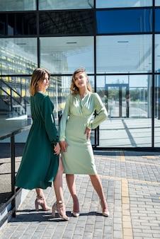 Piękne 2 dziewczyny pozują latem w przyrodzie w przepięknych zielonych sukienkach. portret kobiety