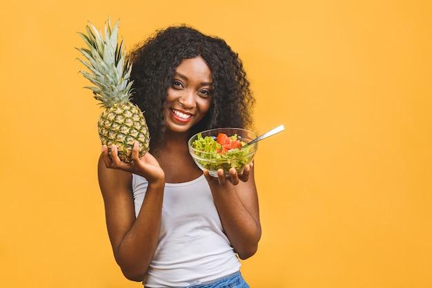 Piękne african american czarna kobieta jedzenie sałatki i ananasa