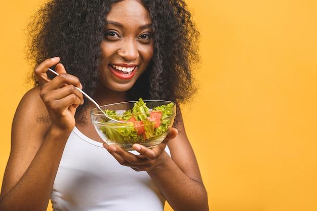 Piękne african american czarna kobieta jedzenie sałatki