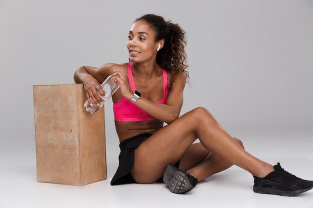 Piękne afro american sportsmenka w słuchawkach odpoczywa siedząc i pije wodę z butelki na białym tle na szarym tle