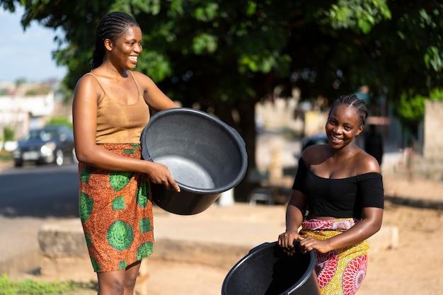 Piękne afrykańskie kobiety bawią się podczas pobierania wody