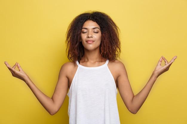 Piękne atrakcyjne kobieta afroamerykanów z modne szklanki księgowania nad żółtym tle studyjny. skopiuj miejsce.