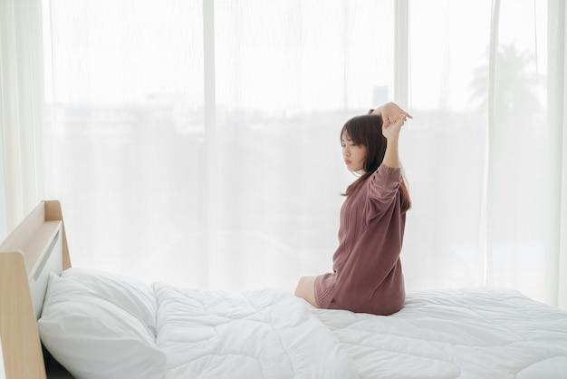 Piękne azjatki na łóżku i budząc się rano