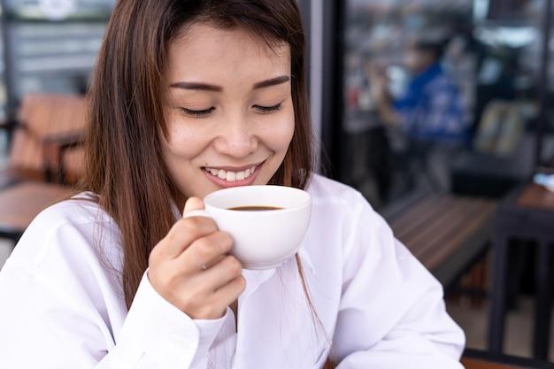 Piękne azjatki piją kawę lub herbatę w relaksu. kobiety są szczęśliwe i cieszą się w kawiarni. koncepcja odpoczynku i relaksu