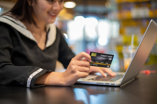 Piękne azjatki trzymające kartę kredytową i telefon komórkowy na zakupy online. uśmiechnięta i szczęśliwa
