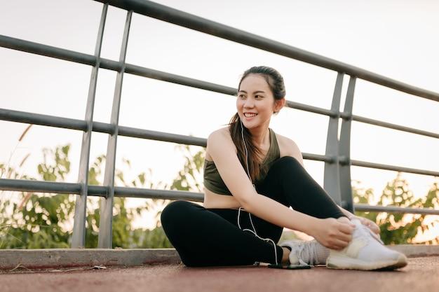 Piękne azjatki w odzieży sportowej, ćwiczenia na świeżym powietrzu w parku podczas zachodu słońca. koncepcja zdrowych kobiet.