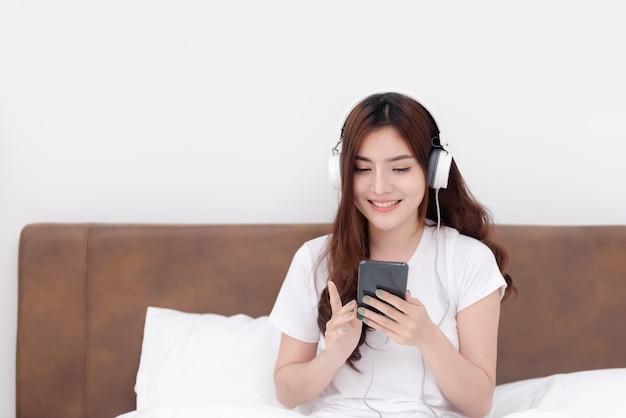 Piękne azjatki w słuchawkach słuchające muzyki przesyłanej strumieniowo ze smartfonów.